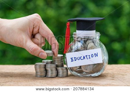 Woman hand holding stack of coins money and glass jar with full of coins and graduates hat label as Education education or savings concept.