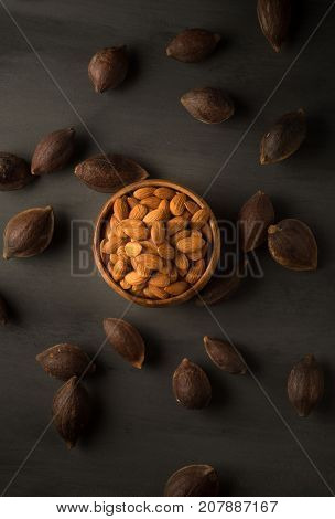 Best quality golden almonds in a bowl surrounded by hard shells of almonds before processing. Almonds are enriched with fiber, protein, vitamin, manganese, magnesium etc.