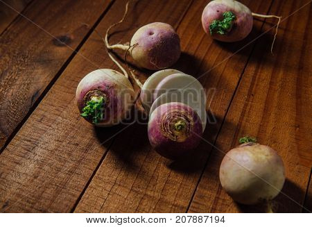 Group of whole and few sliced fresh turnips on a wooden background.