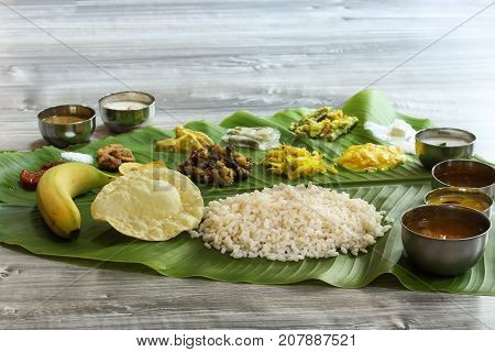 Traditional Kerala Onam Sadya served in Banana Leaf / Vegetarian meal boiled rice curries and Papad served during festivals