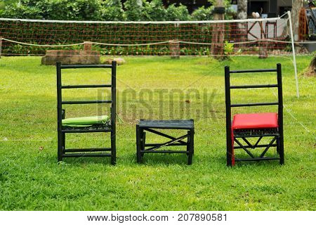 Woden chairs and small table on a green lawn
