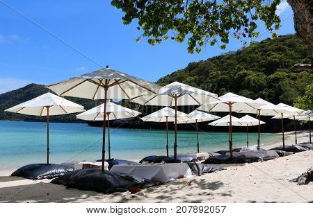 White umbrella and air cushion seat on the beach in Thailand.