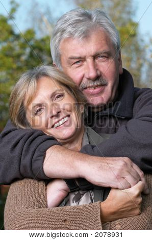 Front view of a happy mature couple. Focus on the woman. poster