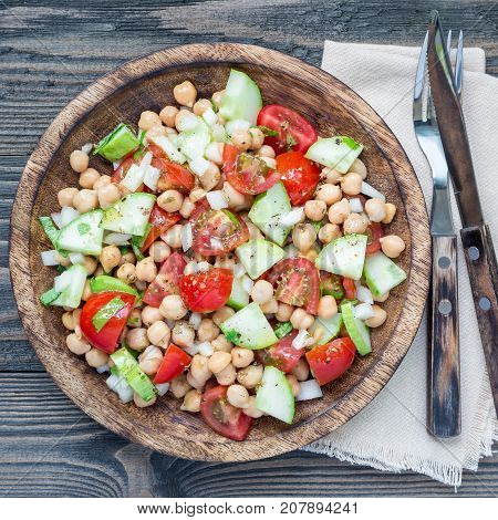Chickpeas salad with cherry tomatoes cucumbers basil and onion with citrus dressing top view square format