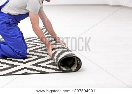 Male worker unrolling carpet indoors