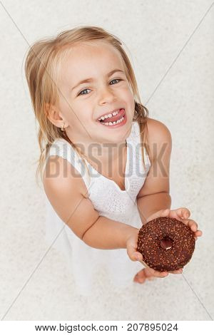 Happy little girl holding a chocolate covered donut - looking up with a broad smile and mischievous eyes