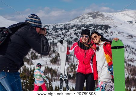 Photographer takes picture of two young women with ski and snowboard on ski holiday in mountains