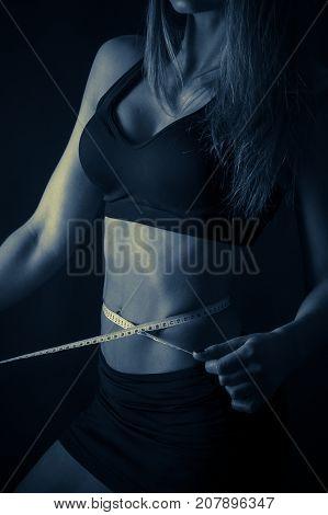 girl measuring waist centimeter on a dark background.