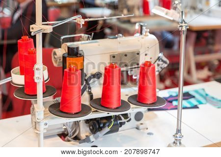 Spools of red threads on sewing machine