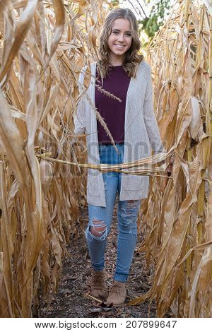smiling Caucasian teenage girl in frayed blue jeans in autumn cornfield