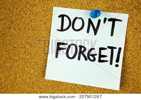 don't forget written on color sticker notes over cork board background business concept