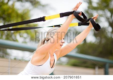 young attractive woman doing upper body exercise training arms using suspension straps outdoor alone