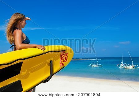 Life saving yellow board with surf rescue sign. Young lifeguard woman stand on duty look at blue sea. Assure swimming people safety. Summer family vacation on ocean beach. Travel background.