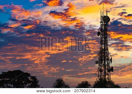 Silhouette Of The Antenna Of Cellular Cell Phone And Communication System Tower On Cloud And Blue Sk