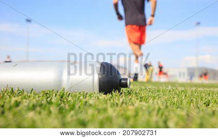 Sport bottle of fresh water energy drink on football field grass.