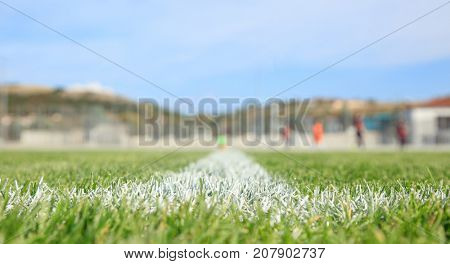 Closeup of painted boundary line of a green soccer field. Blurred players,