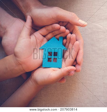 Adult and child hands holding paper house family home and real estate concept