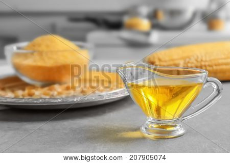 Glass gravy boat with corn oil on kitchen table