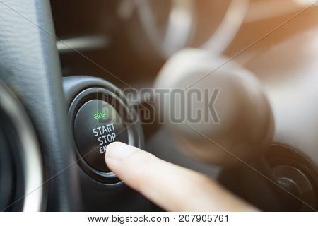 Close up of finger pressing the start/stop engine button on car.