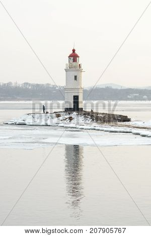 Lighthouse and reflection in sea. Ice in winter.