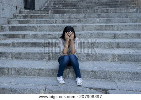 young beautiful and sad Hispanic woman desperate and depressed sitting on urban city street staircase looking confused and lost in life problems and depression concept