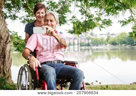 Senior couple in wheelchair, taking selfies with their phone