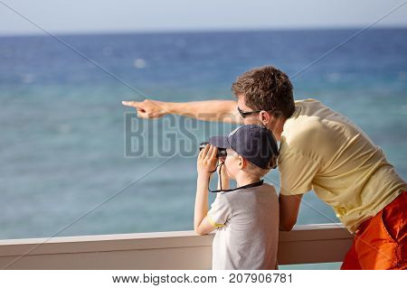 little caucasian boy using binoculars and his young father pointing with finger and showing something exploration and vacation concept