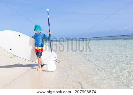 positive smiling boy enjoying stand up paddleboarding active healthy vacation concept wide angle with copy space on right