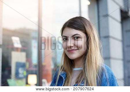 Close up shot of amazing young woman with facial piercing standing outside souvenir shop while shopping in city center looking for present on her boyfriend's birthday. People and urban lifestyle