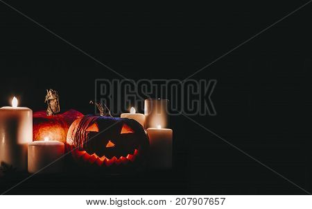 Halloween pampkin on black background with candles and smoke