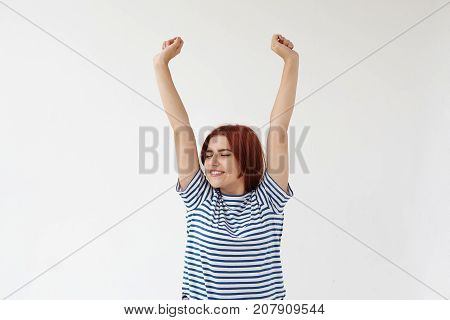 Adorable cute young woman wearing striped pajamas closing eyes with joy and stretching arms in the air weakening up early in the morning ready for new happy day. Youth and happiness concept