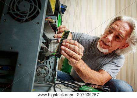Tech savvy Senior man assembling a desktop computer