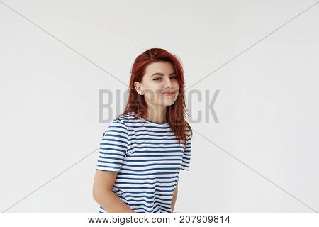 Studio shot of amazing young Caucasian woman wearing trendy sailor's shirt looking at camera with joyful mysterious smile. Enigmatic red haired girl smiling playfully posing at blank grey wall