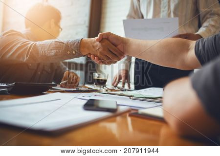 Work together and shake hands between business people and business associates in asia to merger to build good relationships and reconciliation. Is morale in the joint venture.