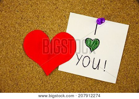 i love you handwritten pinned to a cork notice board with red heart Love concept