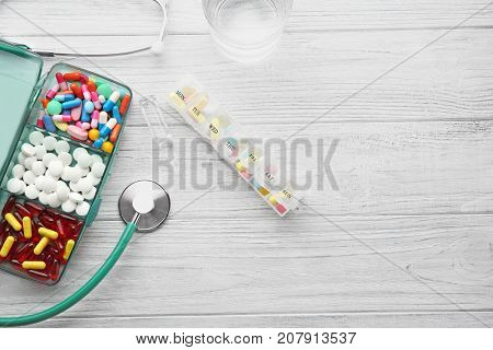 Composition with different pills and stethoscope on wooden background