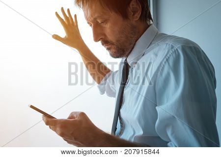 Businessman standing next to office window and using smartphone. Business communication over sms messages or mobile apps. Business person received bad news.