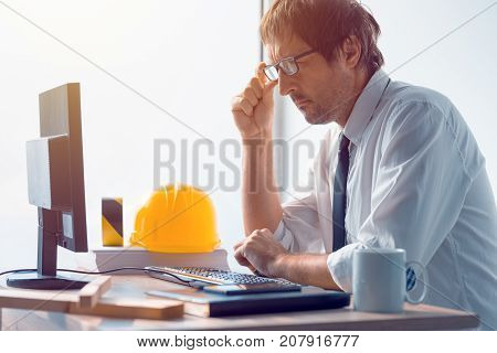 Construction engineer working on desktop computer using CAD software to sketch project in architecture studio office