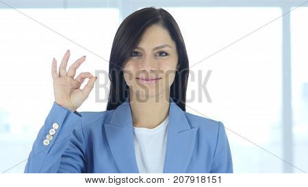 Okay Sign by Young Businesswoman Gesture in Office