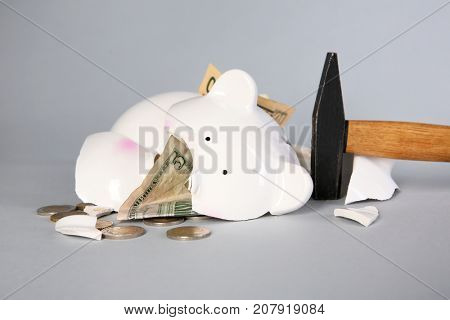 Hammer and broken piggy bank on grey background