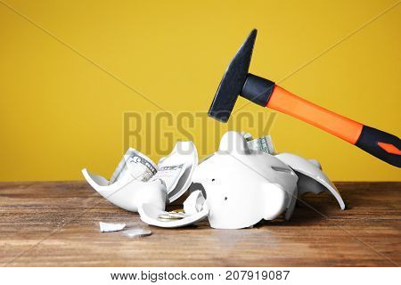 Hammer and broken piggy bank with money on wooden table against color background