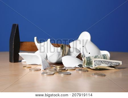 Hammer and broken piggy bank with money on table against color background