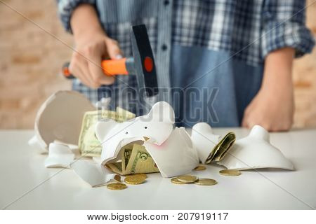 Broken piggy bank and blurred woman with hammer on background
