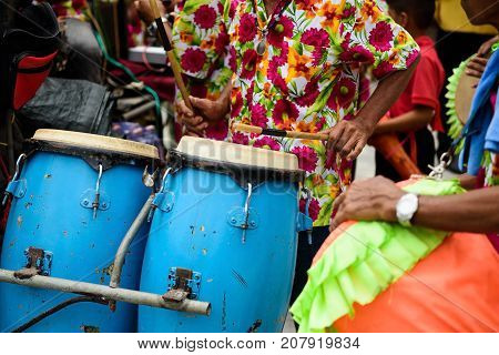 Group of Thai musicians with colorful flower shirt perform Thai traditional drum instruments during Buddhist ordination ceremony in temple. Culture of Thailand to be a monk.