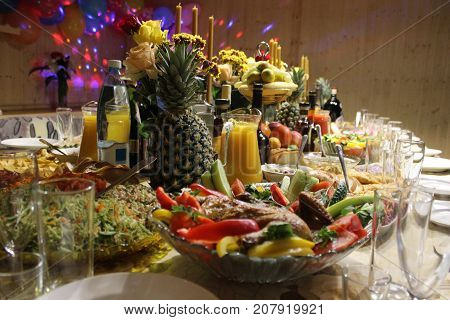 photo covered holiday table with food and liquor candles and evening lighting