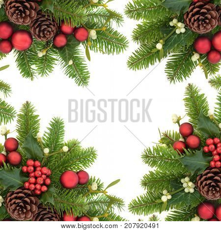Christmas decorative background border with holly ivy, mistletoe, fir, red bauble decorations and pine cones on white.
