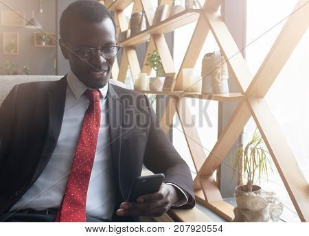 Indoor Photo Of Young African Businessman Spending Lunchtime In Cafe Typing And Chatting On Cellphon