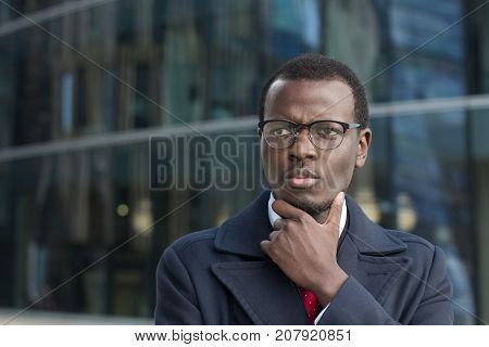 Outdoor Closeup Of Young Dark-skinned Executive In Spectacles Standing In Street, Touching Chin With