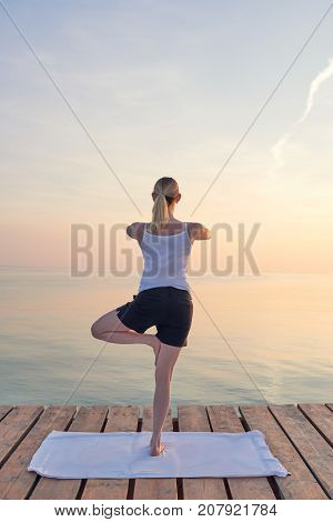 Young Woman Practising Yoga By Sea