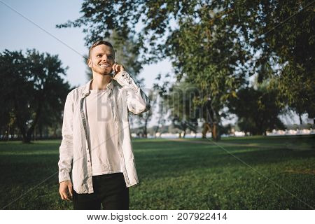 Young and good-looking student is standing in a beautiful green park this summer evening. He desided to have a walk after the lessons at university. Now this man is talking on the phone with somebody, smiling and enjoying the conversation.